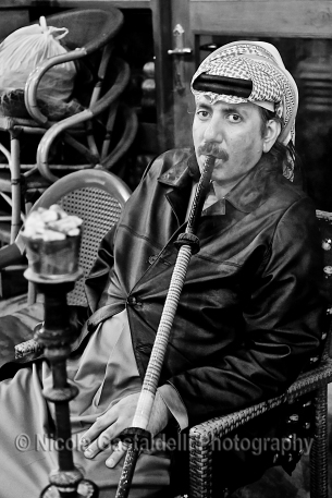 Qatar. A man smoing shisha in the old bazaar.