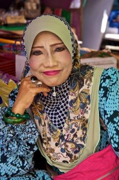 Brunei. Brunei woman smelling at fish market.